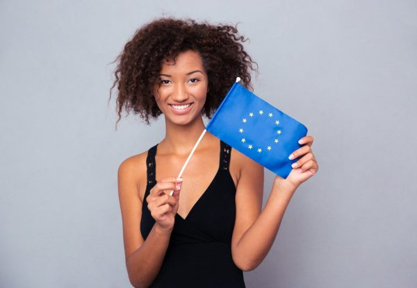 Portrait of a happy afro american woman holding Euro flag over gray background and looking at camera