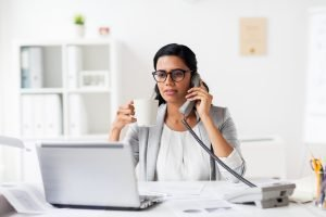 business, technology, communication and people concept - happy smiling businesswoman or secretary calling on phone and drinking coffee at office