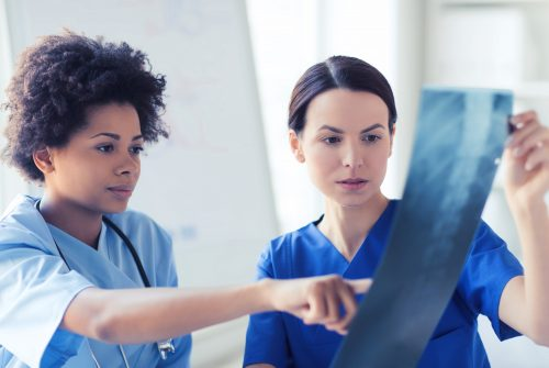 radiology, surgery, people and medicine concept - female doctors looking to and discussing x-ray image at hospital